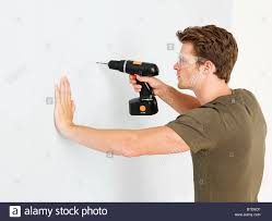 using electric drill. stock photo - young man using electric drill p