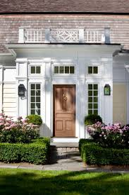 Boxwood hedge border with plantings behind. Beautiful windows and front door .