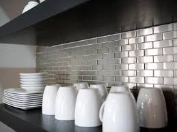 comfortable kitchen ideas with black counter and metallic wall tiles using white cups and wooden floating shelves