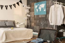 Stylish Bedroom With Large Bed Travel Decorations And Open Suitcase