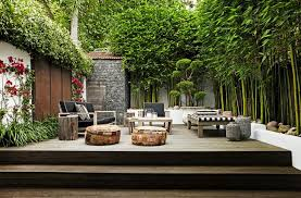 teak steps up to deck boasts teak outdoor sofa and chair covered in navy outdoor cushions facing a teak tail table and a black and white lounger placed