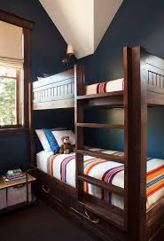 Blue and brown cottage kids' room boasts navy painted walls lined with a  brown bunk bed accented with drawers lined with rope pulls and a built-in  ladder ...