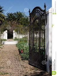 wrought iron garden gate opening on winery s vegetable garden with a second gate in the distant background