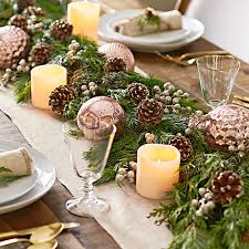 Fresh green holiday garland used as a centerpiece on a dinner table, with  copper-