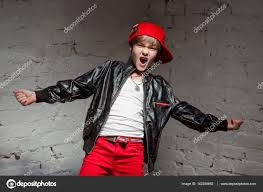 portrait of cool young hip hop boy in red hat and red pants and white shirt and black leather jacket in the loft photo by kateryna mostova