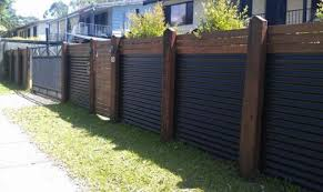 wood and corrugated metal create a very eye catchy and stylish fence