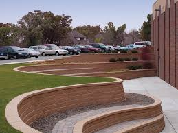 parking lot edged by a curved and terraced diamond pro straight face concrete block retaining wall