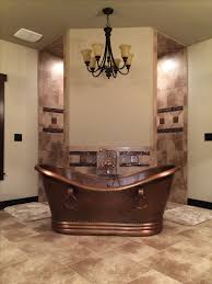 Rustic bathroom, hammered copper tub in front of a corner walk through  shower. Dream