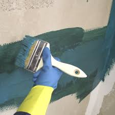 using a 4 inch paint brush to apply waterproof membrane over backer board joints and