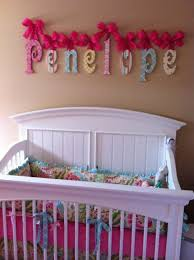 colorful sign above large crib baby name letters for nursery wall red ribbon decoration cute