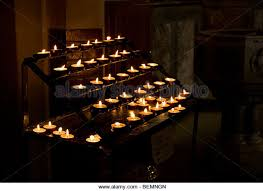a stand of alter candles taken at a roman catholic church during a christening stock alter lighting