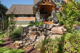 front yard waterfall with boulder landscape shaping and surrounding garden boulder tiny house front