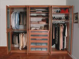 this modern women s clothing features beige finished cabinetry and reddish hardwood flooring along with white walls closet works