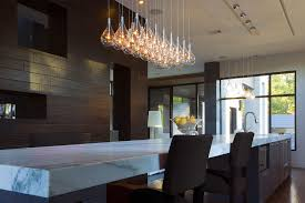 waterdrop shaped modern pendant lighting fixture over a white granite topped kitchen island