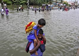 flooding in southeastern disrupts power flights newshour a man carries a girl through flooded streets in chennai on dec