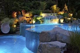 swimming pool lighting options. this luxury swimming pool has cool lighting and a water slide options