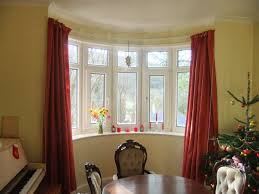 interior red bay window curtains on the yellow wall with round dining table and modern