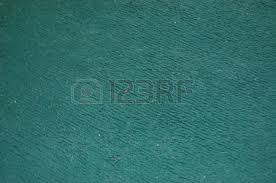 dark green carpet texture. a dirty dark green carpet texture with hair and bits on it. stock photo -