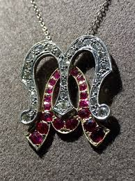 gold pendant with initials m a featuring diamonds and rubies with white gold chain