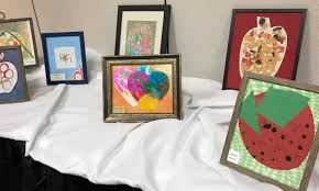 framed childrenu0027s pictures arranged on a table with white tablecloth preschool art29 art