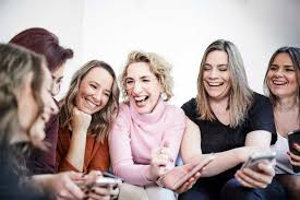 Group of six laughing women with smartphones Stockphoto