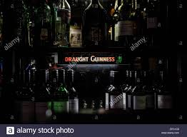 subdued lighting. Subdued Lighting Illuminating Various Bottles Of Wine In A Pub. - Stock Image H