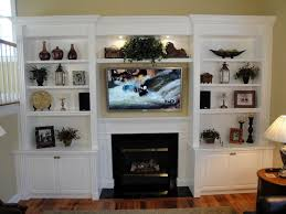 built in shelving unit and cabinets beside the fireplace unit tv set on fireplace box