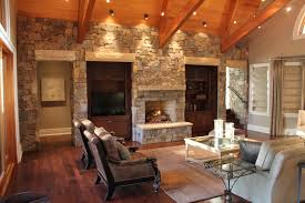 stone wall of natural wood stone combined with glasses coffee table on the cream rug it