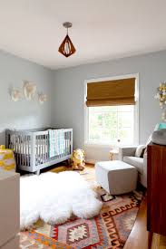 Pale blue kid's room with crib and wall decals - love this Kilim rug. Very