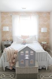 her bed is another jenny lind style like her crib but a little more whimsical i added white ruffle bedding and some sweet pink and peach pom pom pillows