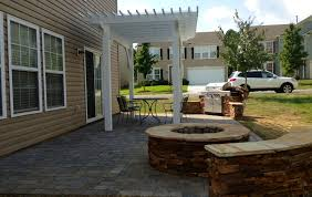 outdoor fireplace paver patio: paver patio with ledge stone fire pit and sitting wall and a wood pergola with an