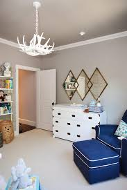 a white faux antlers chandelier hangs from a gray ceiling lighting gold diamond mirrors mounted to a gray wall above a land of nod campaign wide dresser
