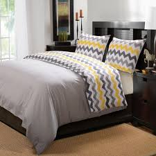 black stained wooden king size bed with yellow and grey chevron pattern duvet cover reverse added side table placed on brown carpet with taupe and gray
