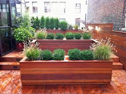 This NYC custom roof garden design features contemporary looking wood  planters, deck, and fence