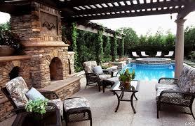 classic backyard patio ideas with brick fireplace facing cozy sofa and aquamarine pool