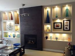 Fireplace Feature Wall with wall niches and dark tiled fireplace More