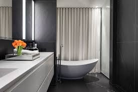 scenic white porcelain soaking freestanding tub also white floating vanity as well as white sliding shower curtain in grey bathroom decoration ideas