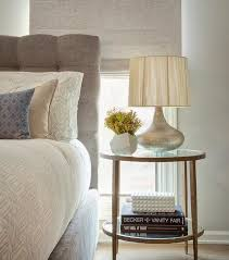 features a gray on tufted headboard on bed dressed in white and gray geometric bedding placed next to a round forged metal and glass bedside table