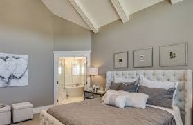 a lovely grey bedroom with white tufted linen headboard the golden photo frames match perfectly