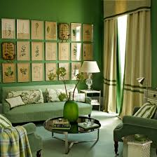 Green living room with striped green and cream sofa, cream curtains and  cream lampshade