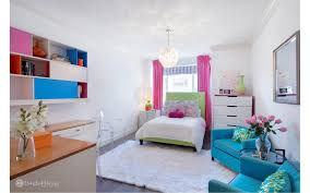 there s also a kids bedroom featuring colorful furniture and a cly rug along with a desk