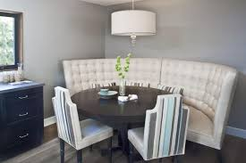 gray and white dining room ideas. curved tufted white dining settee with black round wood table plus flowers and unique chairs also gray room ideas