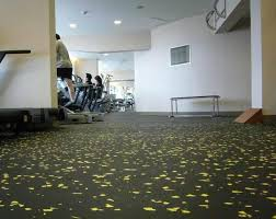 grey patterned rubber gym flooring with small bench under frosted glass ventilation also ceiling lamps