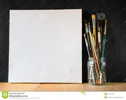 paint brushes in jar and blank canvas over blackboard background royalty free stock photo
