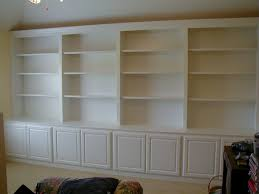 full wall unit white shelves and cupboards
