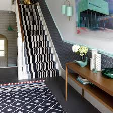 Hallway with monochrome striped staircase runner and geometric rug