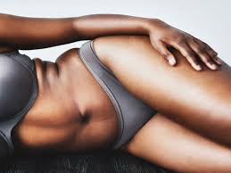 a woman laying down in her bra and underwear