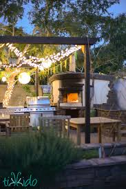 wood fired pizza oven with a fire inside framed by an outdoor kitchen and eating