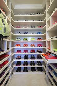 Walk in workout closet features floor to ceiling custom shelves with shoe  cubbies over pull out shoe shelves.