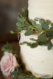 Close Up Of Wedding Cake With Greenery And Pink Rose Stock Photo